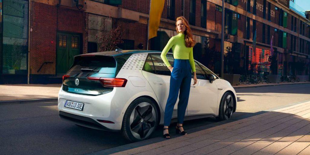 VW ID.3 Frau steht vor dem Elektroauto in der Stadt