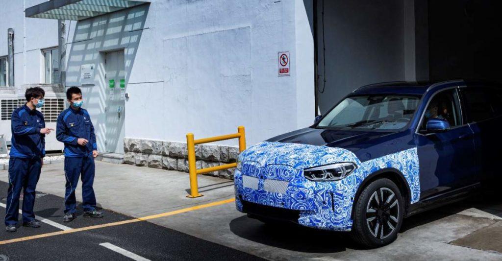 Zwei Mitarbeiter beguchtachten den BMW iX3 beim Verlassen der Produktionshalle