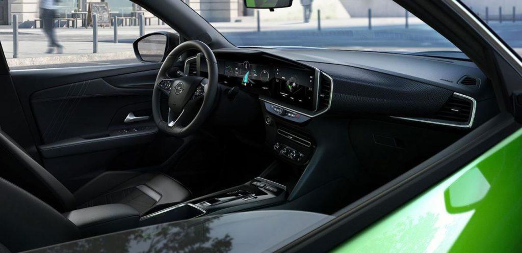 Blick von außen durch das geöffnete Beifahrerfenster auf das Cockpit des Opel Mokka-e