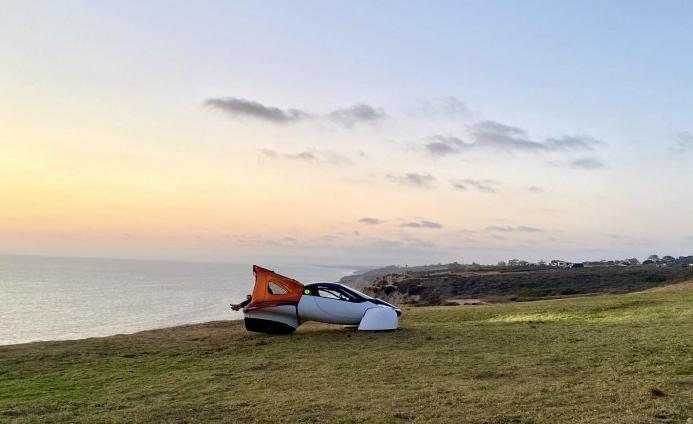 Solarauto Aptera Sol mit aufgebautem Zelt am Heck vor einer Küste