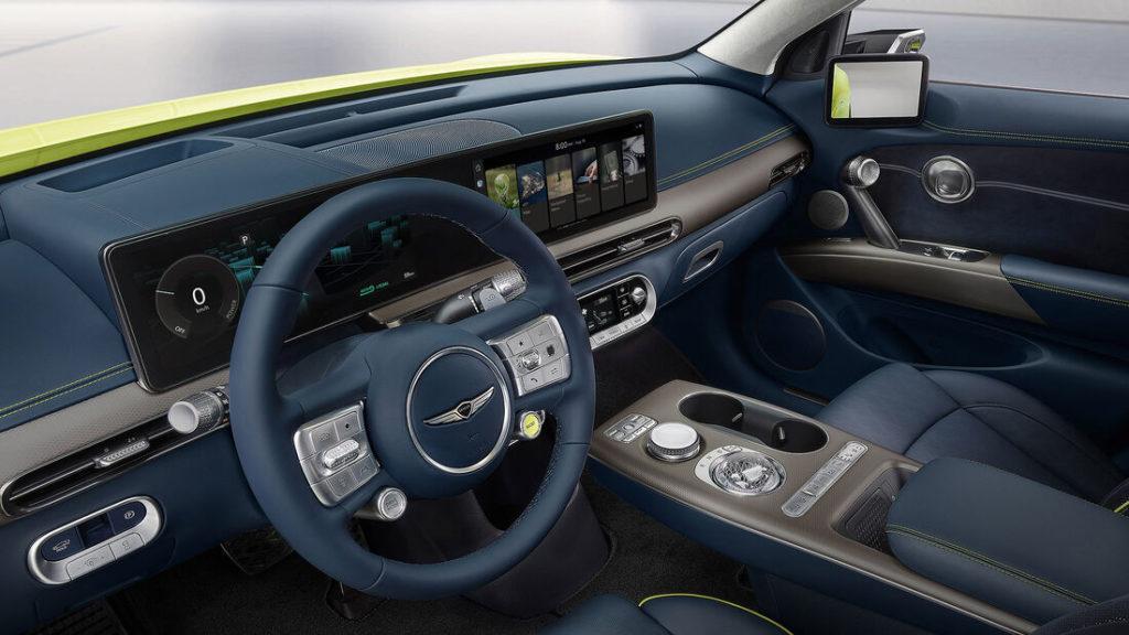 Innenraum des Elektroautos Genesis GV60 mit runden Formen und einem Zwei-Speichen-Lenkrad