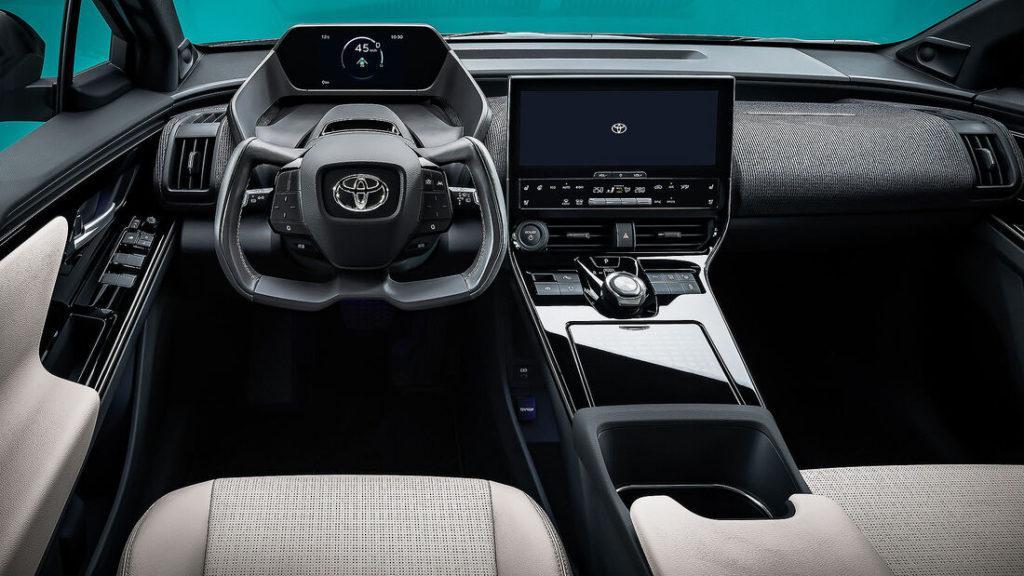 Innenraum des Elektroautos Toyota bZ4X mit eckigem Lenkrad und Bildschirm